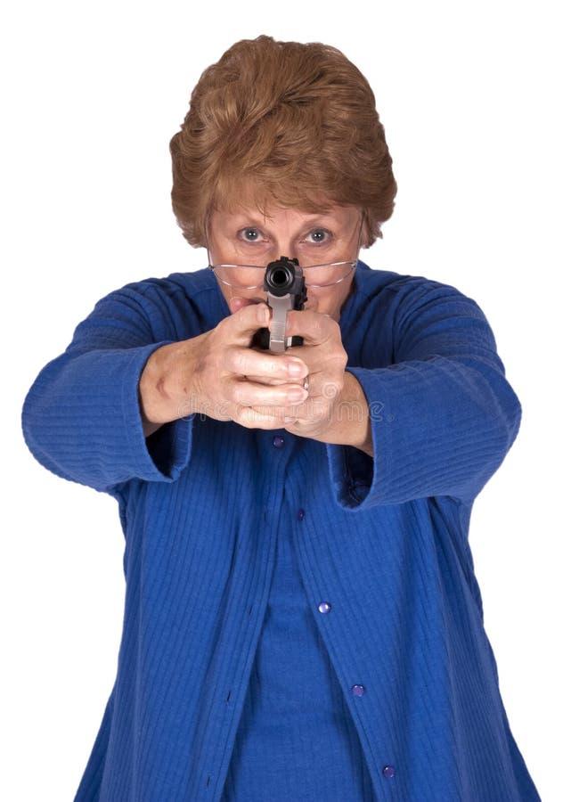 Pistola mayor madura del arma de la mano del asimiento de la abuela de la mujer imagen de archivo libre de regalías