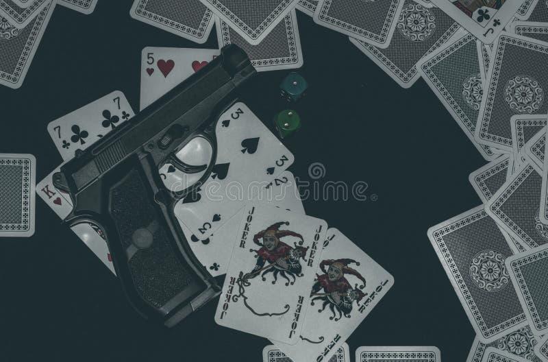 Pistola na tabela com cartões imagens de stock royalty free