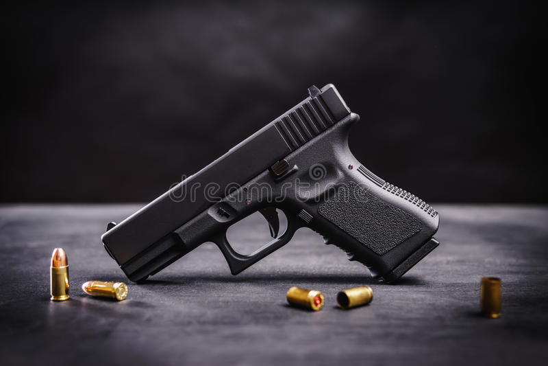 Pistola nera su una tavola nera immagini stock