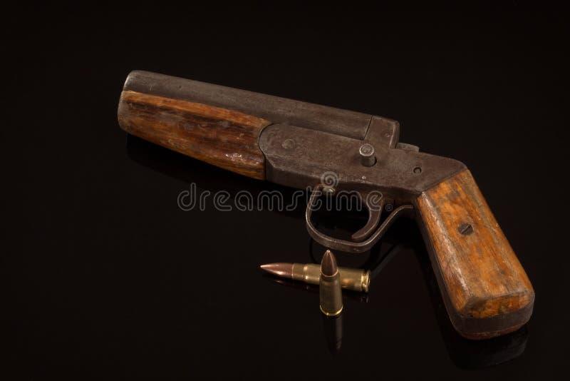 Pistola retra de la arma de mano del vintage y dos balas aisladas en fondo negro fotografía de archivo
