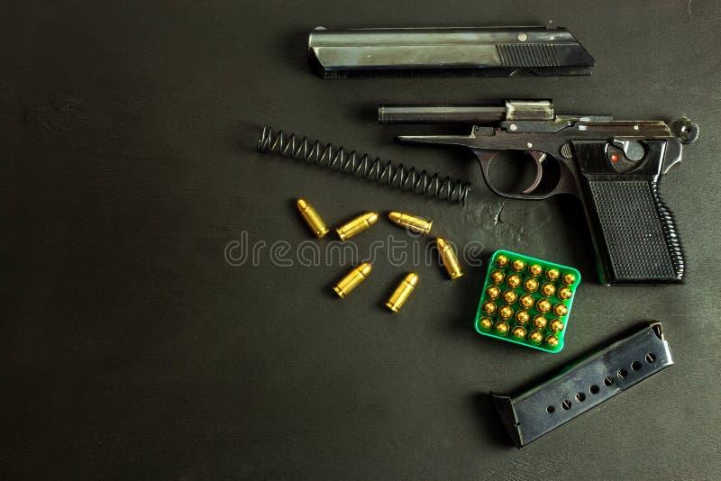 Pistola smontata su fondo nero Parti separate della pistola Pistola e cartucce sulla tavola Destra tenere una pistola immagini stock libere da diritti