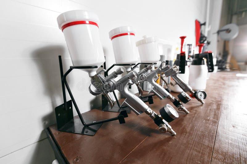 Pistola a spruzzo sulla tavola di legno Nel servizio automatico usato per pittura e mano industriali immagini stock libere da diritti