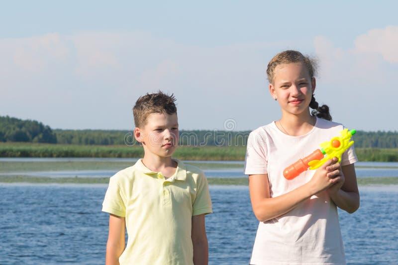 Pistolas de água do jogo do irmão e da irmã no rio foto de stock