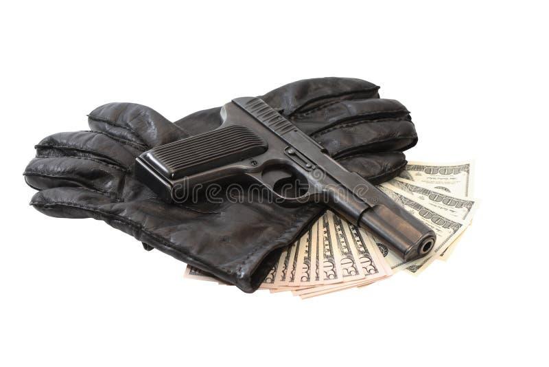 Pistole auf Handschuhen und Geld lizenzfreie stockfotografie