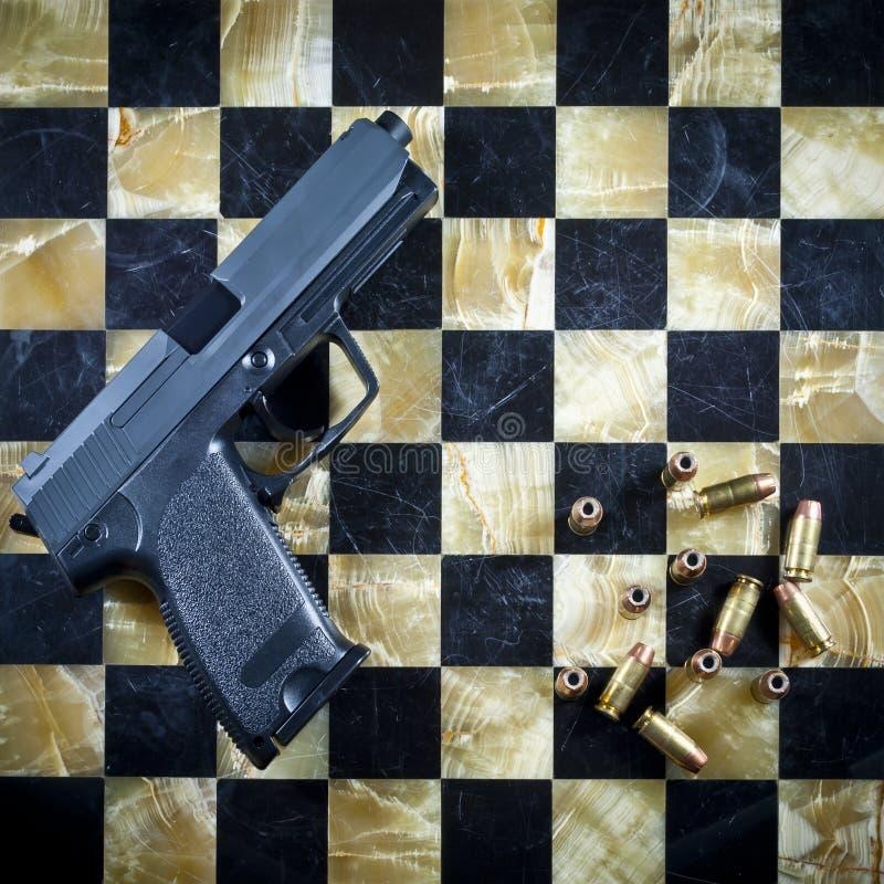 Pistole und Gewehrkugeln auf Checkered Schach-Tabelle stockbilder