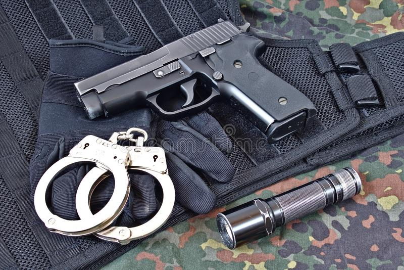 Pistolecik z kajdankami, rękawiczkami i latarką na, taktycznej kamizelce i kamuflaż odzieży obrazy stock