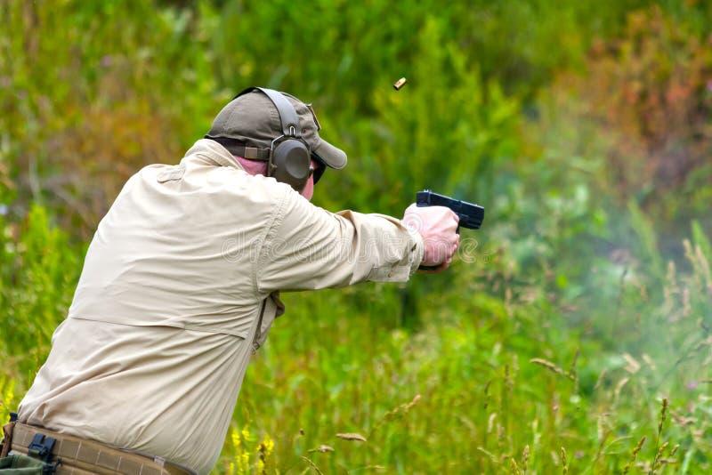 Pistolen-tireur, der um abfeuert lizenzfreies stockbild