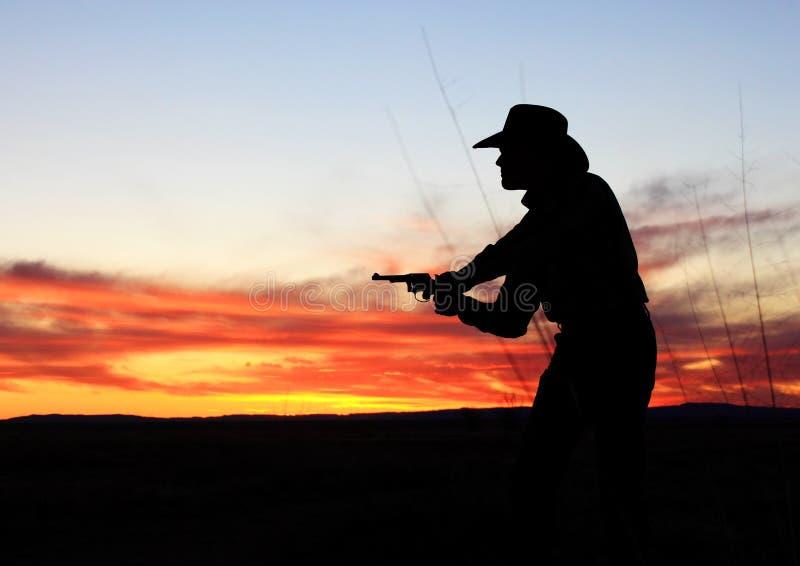 Pistolenheld-Sonnenuntergang lizenzfreie stockfotografie