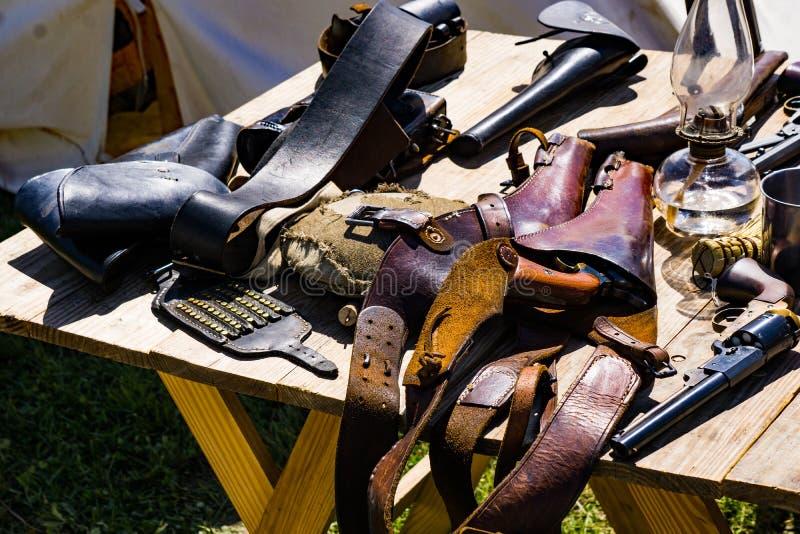 Pistoleras de las pistolas en una tabla imagenes de archivo