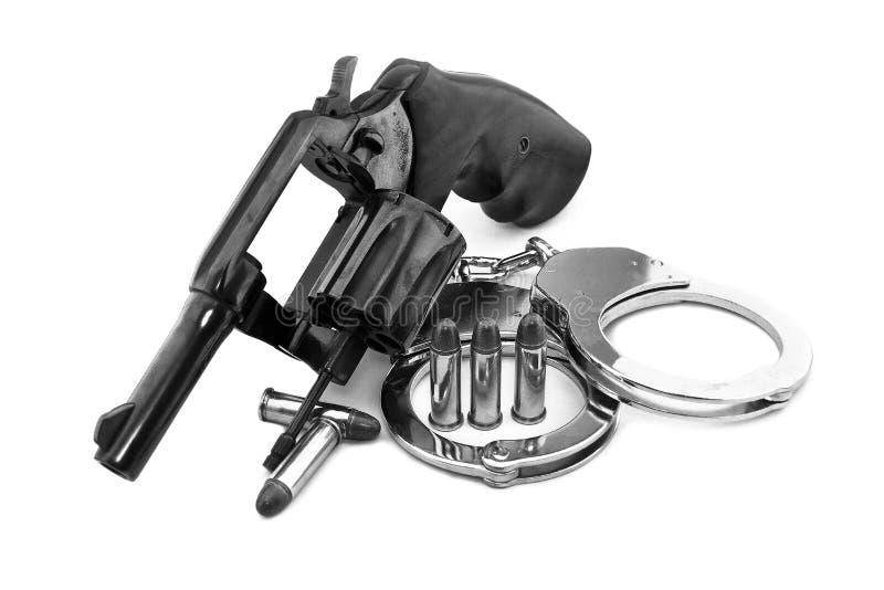 Pistolerevolver und Polizeihandschellen mit Gewehrkugeln lizenzfreie stockbilder