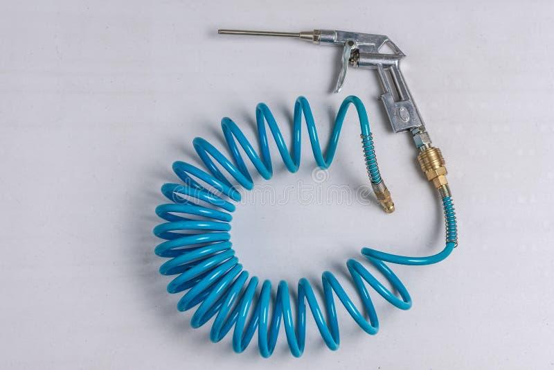 Pistolet à air comprimé de compresseur d'air avec le tuyau bleu enroulé photos stock