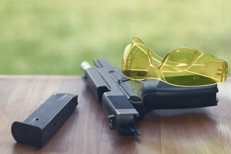 Pistolet avec des verres de sûreté sur un fond en bois images stock