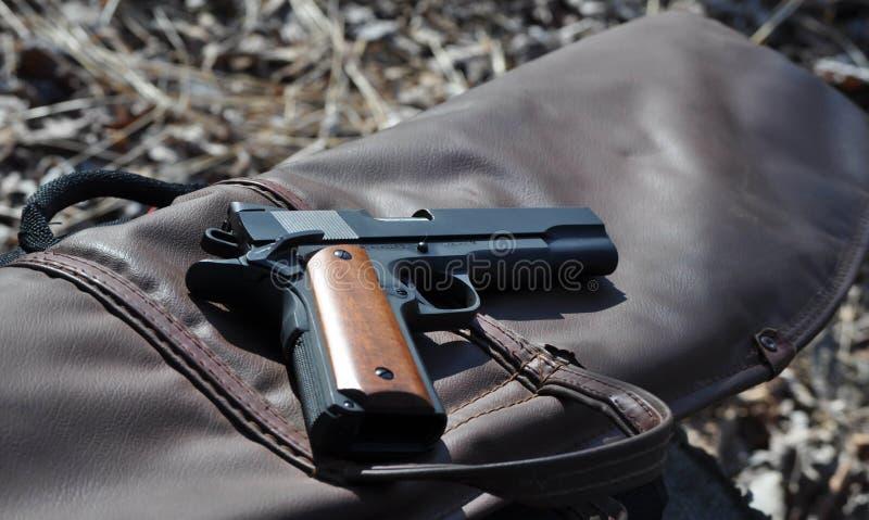Pistolet de 45 calibres placé sur une caisse d'arme à feu en cuir images libres de droits