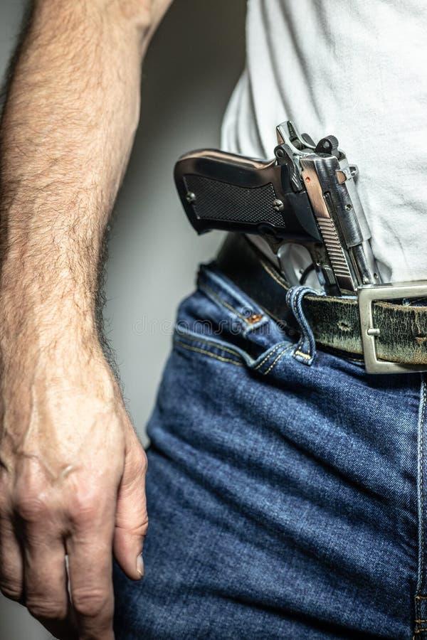 Pistolet de l'argent 9mm dans la ceinture de l'avant avec le bras et la main dessus image libre de droits