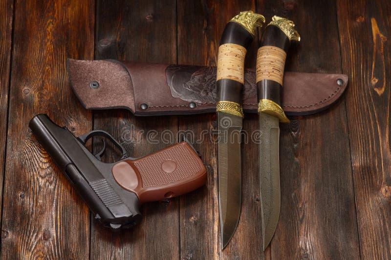 Pistolet i łowieccy Damascus stali noże na drewnianym tle fotografia stock
