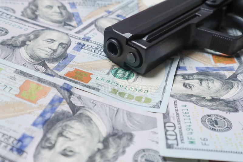 Pistolet na banknocie 100 dolarów, nielegalne pieniądze gangstera, brudny przestępca i terroryzm zdjęcie stock