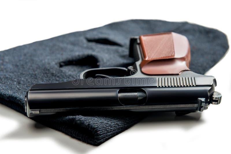 pistolet na czarnym balaclava zamkniętym w górę bielu na obrazy royalty free