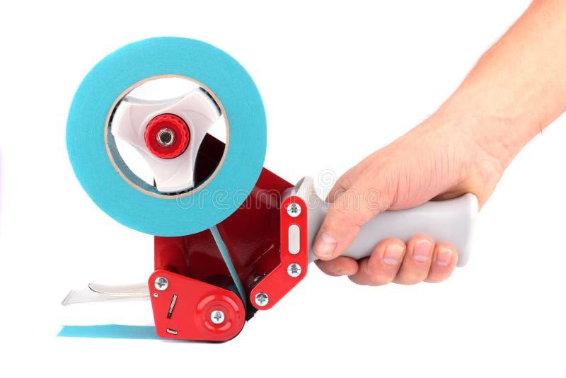 Pistolet rouge avec un ruban adhésif dans une main photos libres de droits