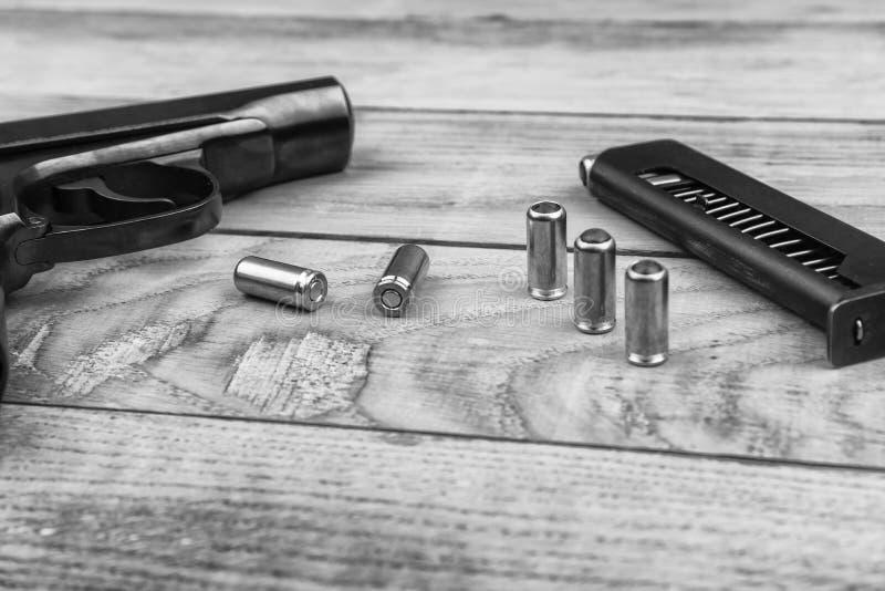 Pistolet traumatique avec des balles et cartouche sur la surface en bois, noire et blanche photographie stock