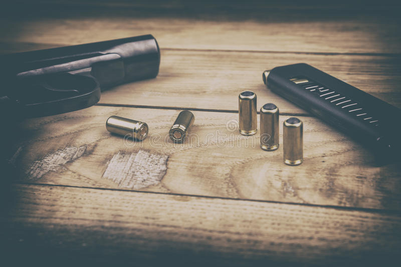 Pistolet traumatique avec les balles et la cartouche sur la surface en bois, effet de vintage photographie stock