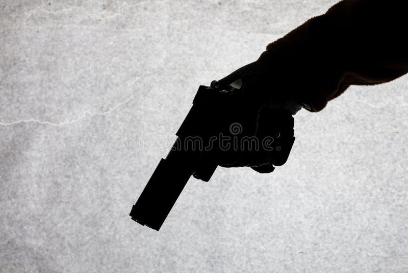 Pistolet w ręce która jest gotowa strzelać przy jego ofiarą mężczyźni Łamać przestępstwo i prawo Atak z bronią Suluet na a fotografia stock