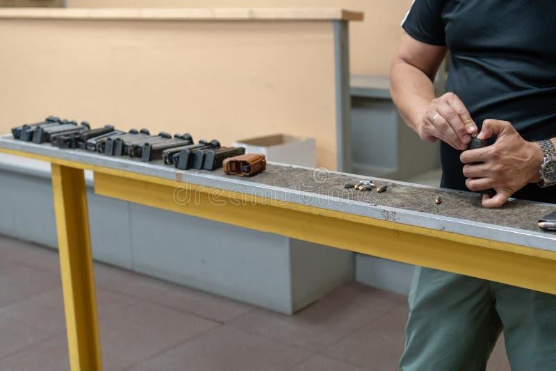 Pistoletowy właściciel z 9 19 ładownicami Ręki mężczyźni ładują pistolet z amunicjami zdjęcia royalty free