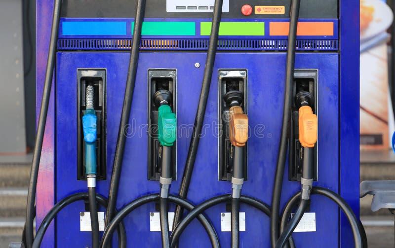 Pistolets multi de carburant de couleur sur la station de carburant photographie stock