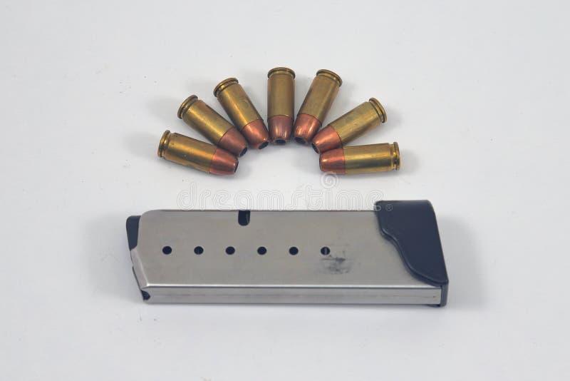 Pistoltidskrift och ammunitionar på vit bakgrund royaltyfri bild