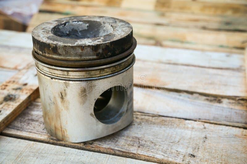 Piston de moteur sur le fond en bois, industrie de pièces d'auto et fond de pièces de rechange, dommages de piston dans les durs  photographie stock