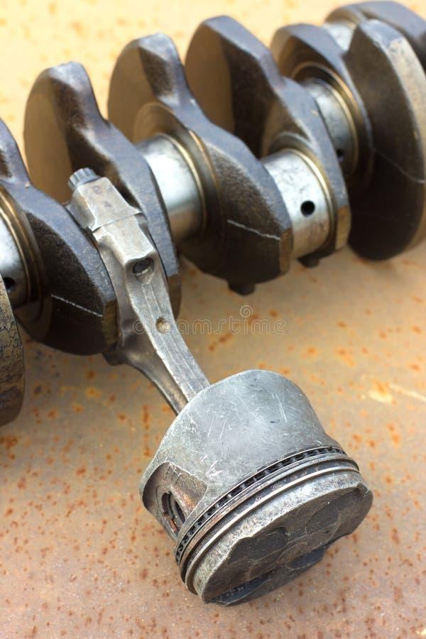 Piston usé à la bielle et au vilebrequin se trouvant sur un métal rouillé image stock