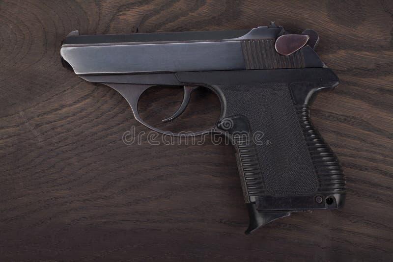 pistool op de houten lijst stock afbeelding