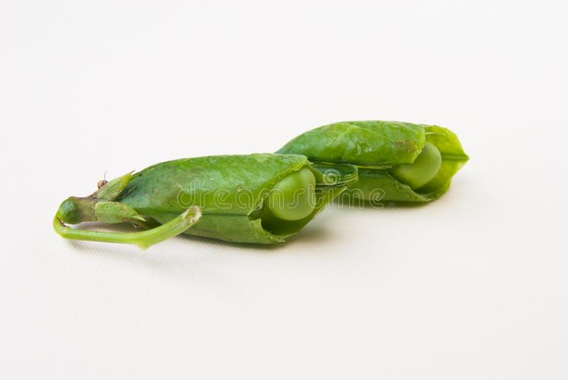 Close-up of fresh green peas opened. Pisum sativum with pod broken into two pieces on white background royalty free stock photo
