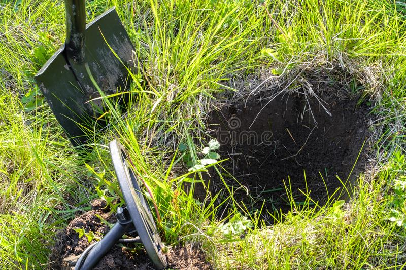 A pit dug in search of treasure, a metal detector and a shovel on a green glade royalty free stock image