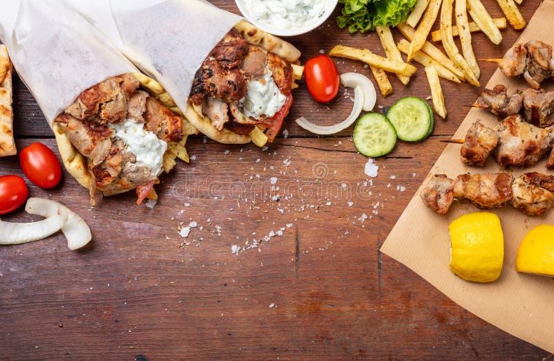 Pita γυροσκοπίων, shawarma, souvlaki Δύο περικαλύμματα ψωμιού pita και οβελίδια κρέατος στον ξύλινο πίνακα στοκ φωτογραφίες