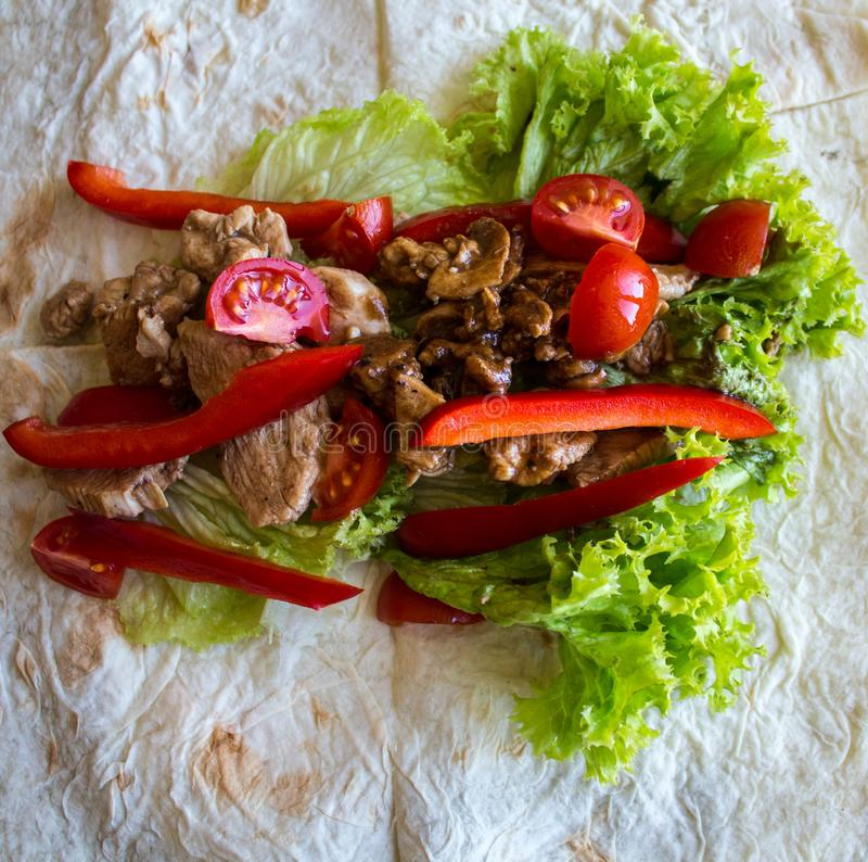Pita bread with grilled meat tomatoes pepper and salad. A pita bread with grilled meat tomatoes pepper and salad stock photography