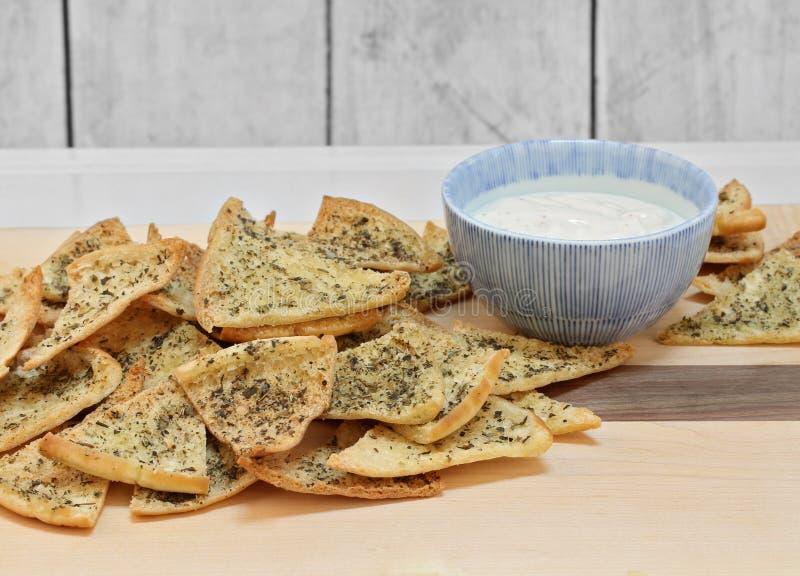Pita Chips temperada com mergulho em uma placa de corte imagens de stock