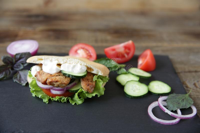 Pita - sandwich, sabiche stuffed with chicken, tomatoes, cucumbers, salad on a black plate and wooden background royalty free stock photo