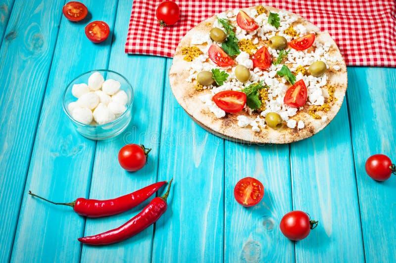 Pita z serem, czereśniowymi pomidorami, oliwkami i greenery na błękitnym drewnianym tle, zdjęcia royalty free