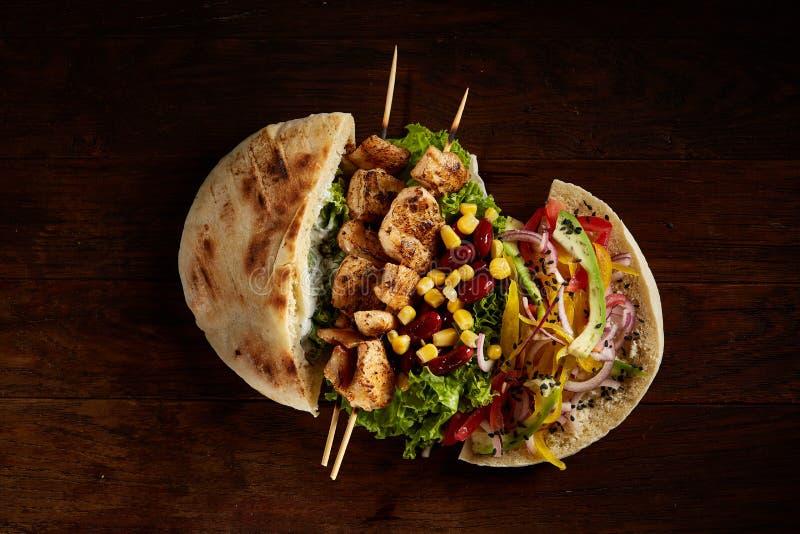 Pitabröd som är välfylld med höna, grönsaker och kebab på träbakgrund, bästa sikt, selektiv fokus royaltyfri fotografi