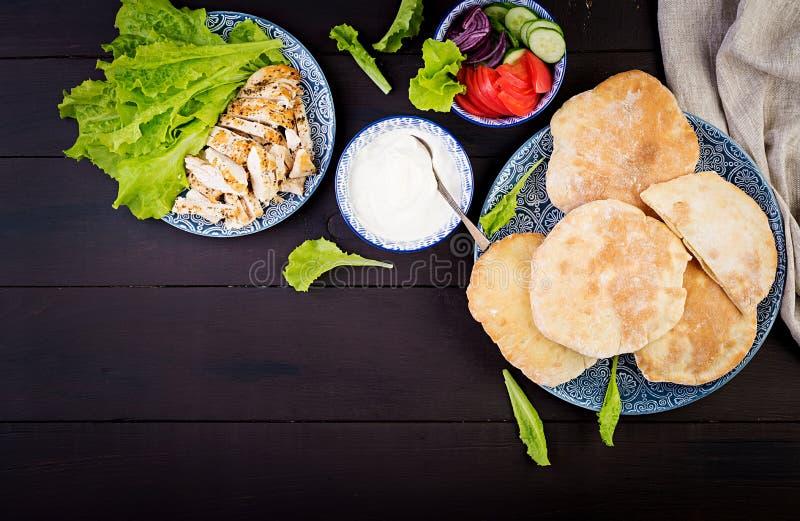 Pitabröd som stoppas med höna, tomaten och grönsallat på träbakgrund fotografering för bildbyråer
