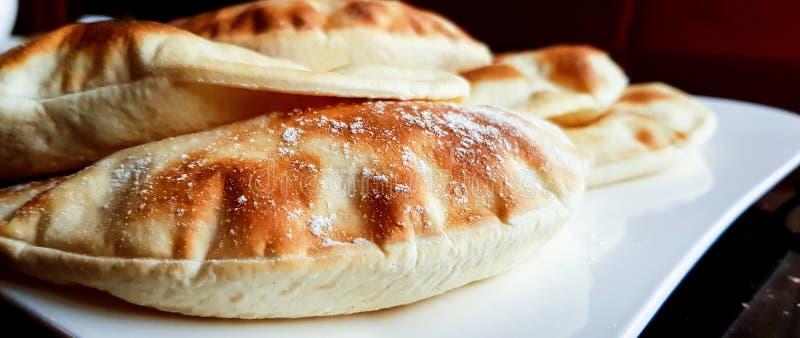 Pitabrödloaves, arabiskt plant bröd som ätas vanligt med såser och dopp liksom hummus och labneh arkivfoto