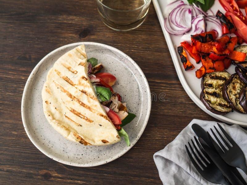 Pitabroodje met geroosterd groenten, paprika, aubergine, tomaat, kip en basilicum met saus Een lijst voor diner wordt gediend dat stock foto