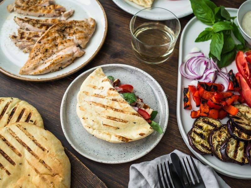 Pitabroodje met geroosterde groenten, paprika, ruwe ui, aubergine, tomaat, kip en basilicum met saus Een lijst voor diner wordt g stock afbeelding