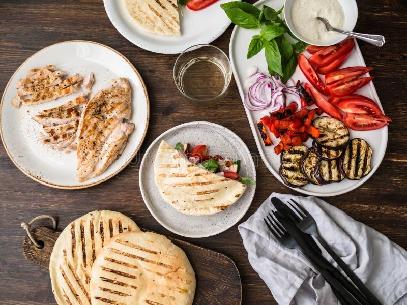 Pitabroodje met geroosterde groenten, paprika, ruwe ui, aubergine, tomaat, kip en basilicum met saus Een lijst voor diner wordt g royalty-vrije stock foto's