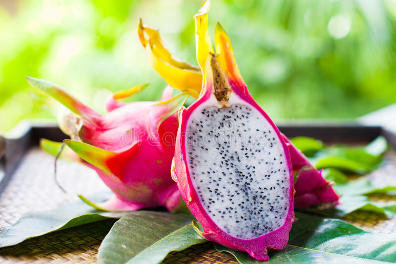 Pitahaya with leaves. On wooden background royalty free stock photo