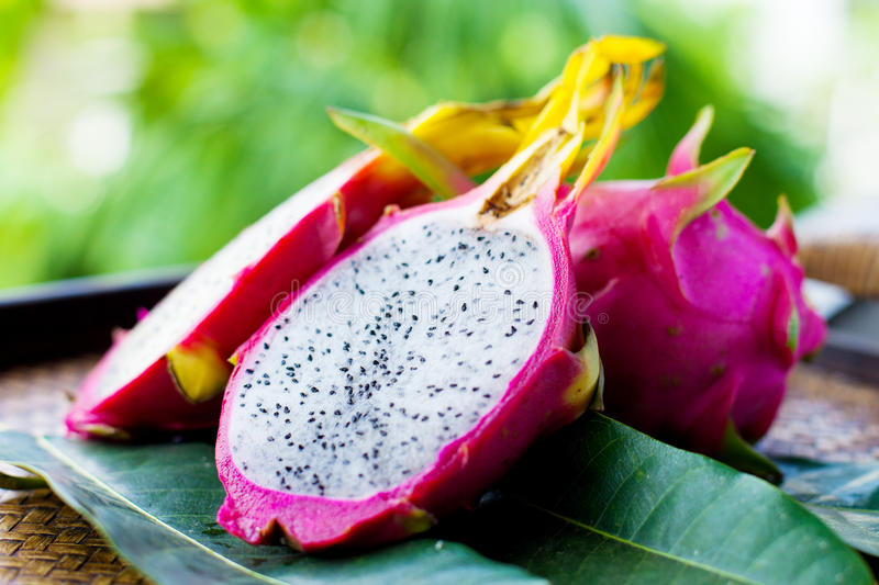 Pitahaya with leaves. On wooden background royalty free stock images