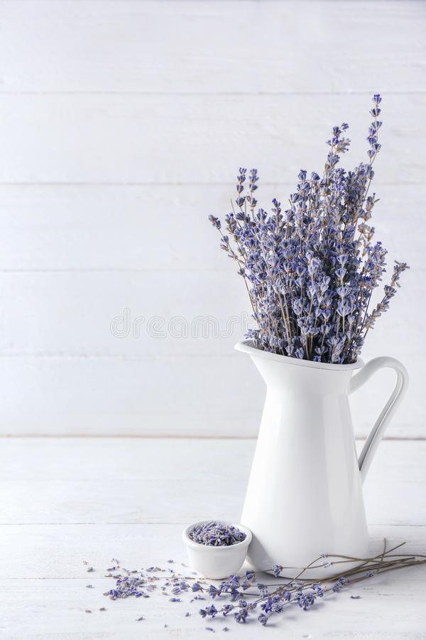 Pitcher with beautiful lavender flowers on white wooden table royalty free stock photography
