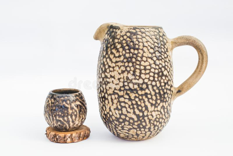 Pitcher and ceramic stoneware tumbler with white background stock photo