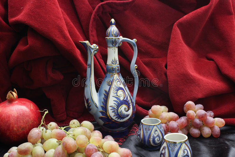 Pitcher and fruits. Pomegranate, grapes. stock photography