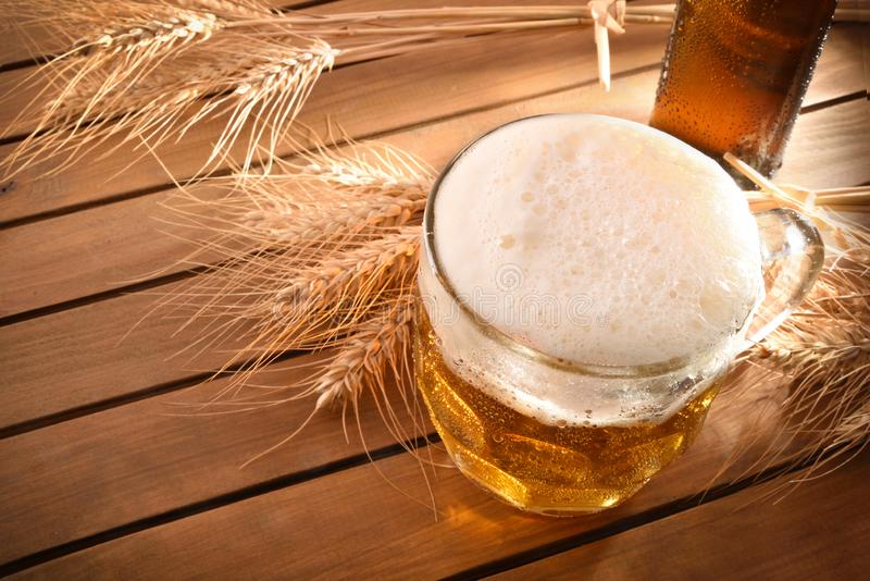 Pitcher full of beer with foam on wood top view stock images
